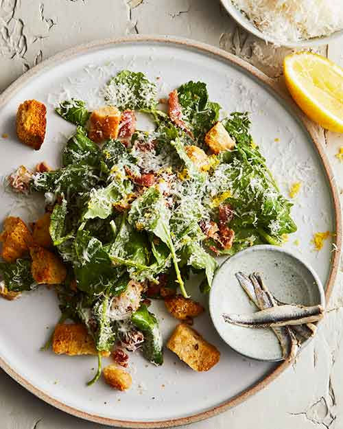 Overview picture of Caesar Salad with slice of lemon and achovies